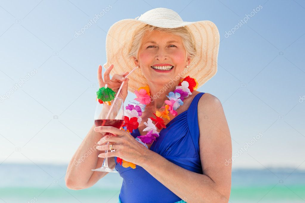 Elderly woman drinking a cocktail on the beach — Stock Photo #10853104