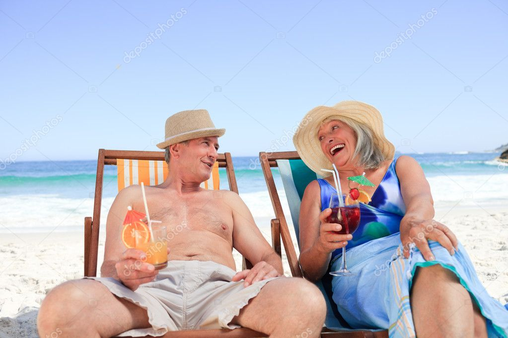Senior couple sitting on deck chairs — Stock Photo #10853816