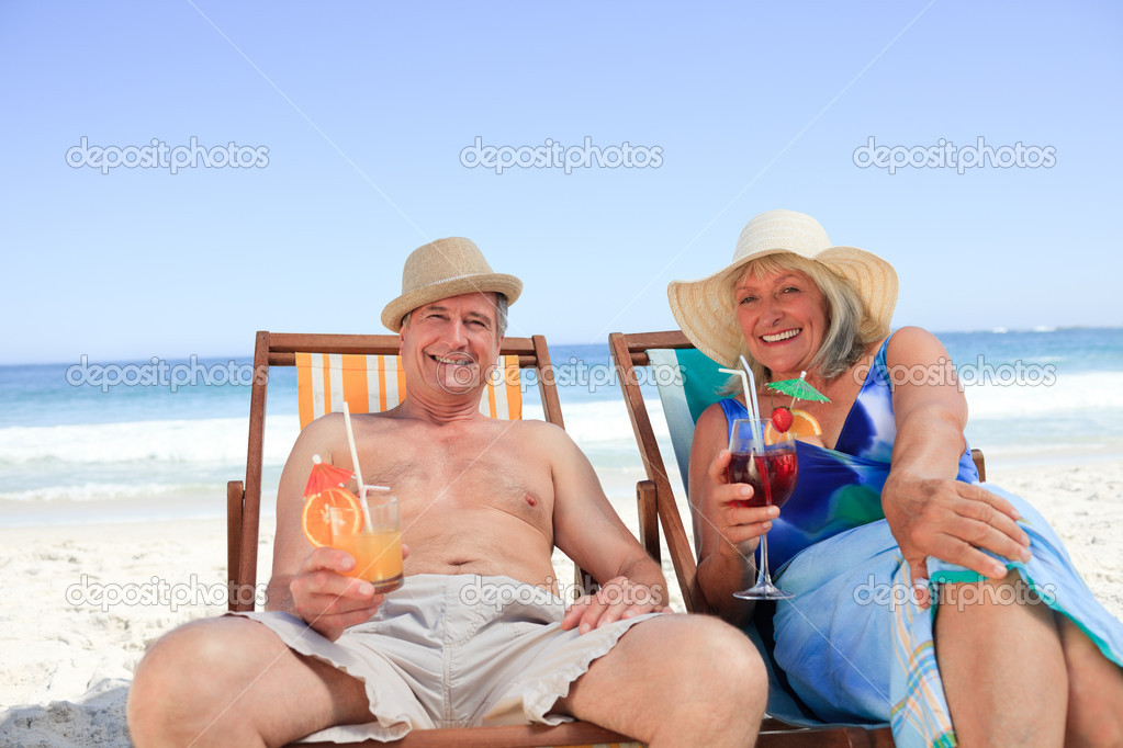 Mature couple sitting on deck chairs — Stock Photo #10853818