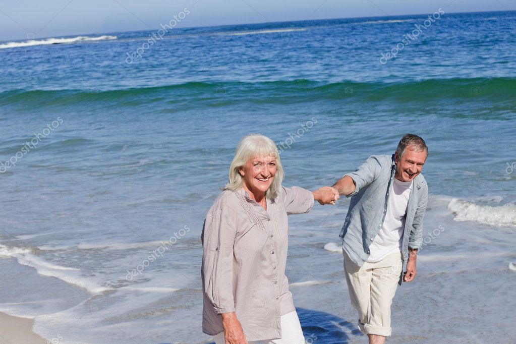 Elderly couple walking on the beach — Stock Photo #10853822