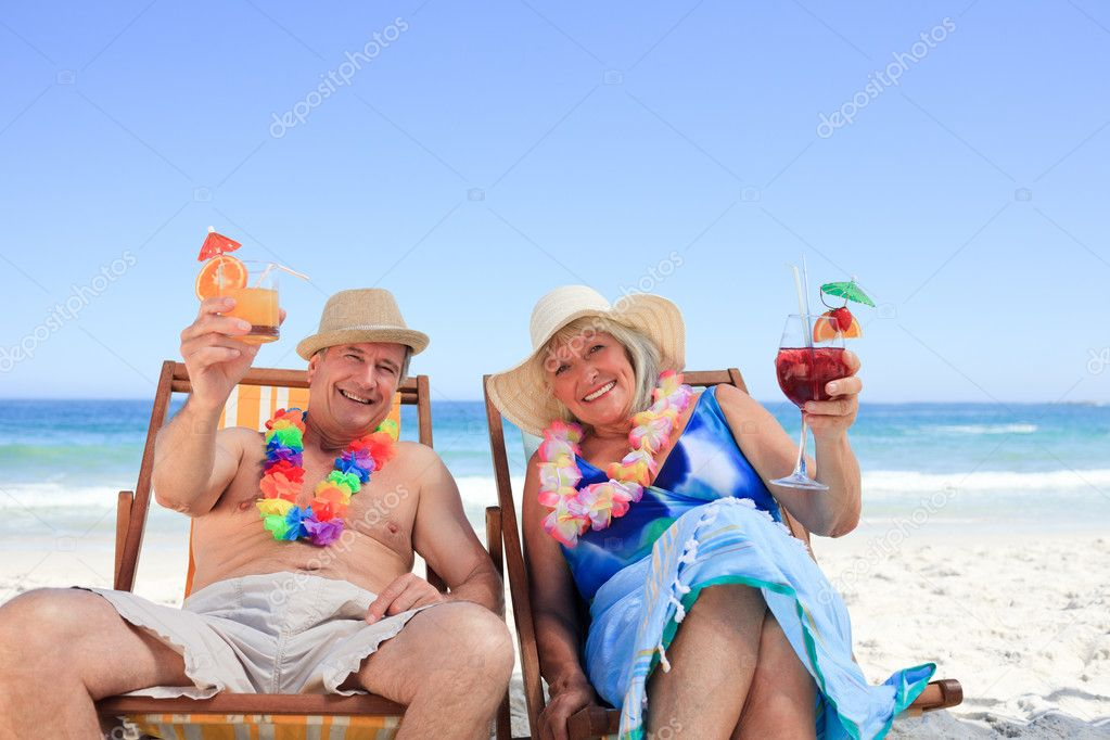 Mature couple sitting on deck chairs — Stock Photo #10853826