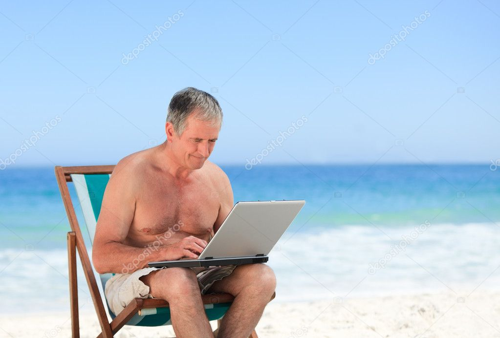Retired man working on his laptop on the beach  Stock Photo #10853832