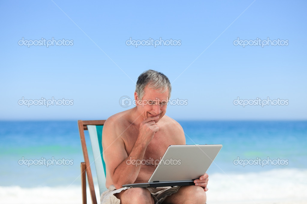 Retired man working on his laptop on the beach  Stock Photo #10853837