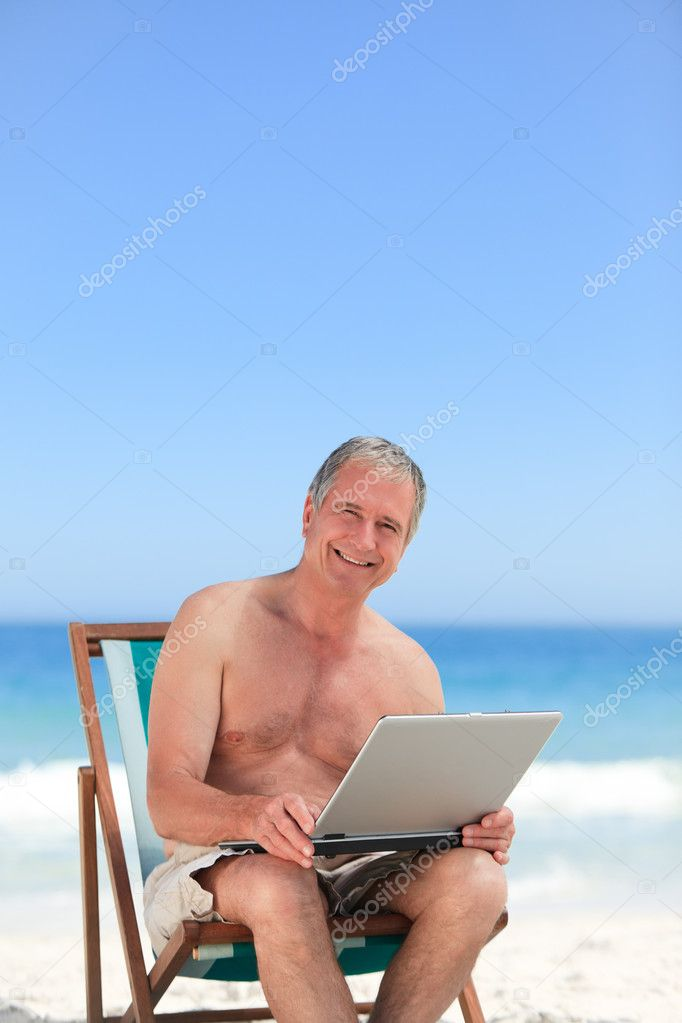 Retired man working on his laptop on the beach — Stock Photo #10853839