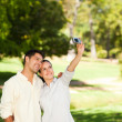 Young couple taking a photo of themselve - Stock Photo