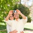 Couple taking a photo of themselve - Stock Photo