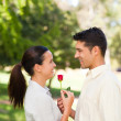Happy man offering a rose to his girlfriend - Stockfoto