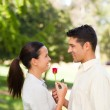 Happy man offering a rose to his girlfriend - Stock Photo