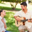 Mplaying guitar for his girlfriend — Zdjęcie stockowe #10860380