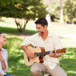 Man playing guitar for his girlfriend - Stock Photo