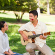 Foto Stock: Man playing guitar for his girlfriend