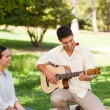 Man playing guitar for his girlfriend - Stockfoto