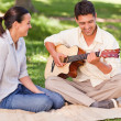 Romantic man playing guitar for his wife — Stock Photo