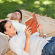 Couple reading in the park - Stok fotoğraf