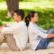 Couple sitting back to back in the park — Stock Photo #10860434