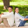 Couple sitting back to back in the park — Stock Photo #10860439