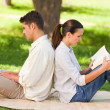 Man working on his laptop while his wife is reading — Stock Photo #10860443