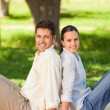 Couple sitting back to back in the park — Stock Photo #10860464