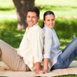 Couple sitting back to back in the park — Stock Photo #10860467