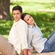 Lovers sitting back to back in the park — Stock Photo