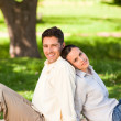 Lovers sitting back to back in the park — Stockfoto
