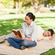 Stock Photo: Womreading while her husband is sleeping