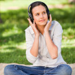 Stock Photo: Happy young woman listening to music