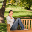 Young beautiful woman phoning on the bench — Stock Photo