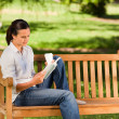 Young woman reading on the bench — Stock Photo