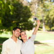 Couple taking a photo of themselve — Stockfoto