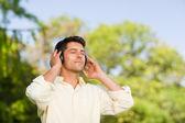 Hombre escuchando música en el parque — Foto de Stock