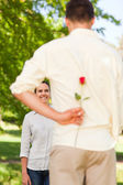 Happy man offering a rose to his girlfriend — Stock Photo