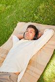 Genç adam parkta müzik dinlemek — Stok fotoğraf