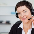 Close up of a smiling secretary calling with a headset — Stock Photo