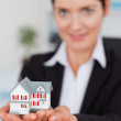 Stock Photo: Businesswoman holding a miniature house