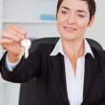 Portrait of a cute secretary showing keys — Stock Photo