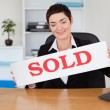 Real estate agent with a sold panel — Stock Photo