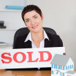 Real estate agent with a sold panel and houses miniatures — Stock Photo
