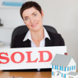 Portrait of a real estate agent with a sold panel and houses min — Stock Photo