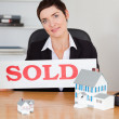 Stock Photo: Female real estate agent with a sold panel and houses miniatures