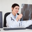 Professional female doctor holding a set of X-ray — Stock Photo #11178881