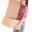 Beautiful woman looking inside a cardboard box while standing — Stock Photo #11179204