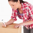 Portrait of a beautiful woman writing on cardboard boxes with a — Stock Photo