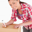 Portrait of an attractive woman writing on cardboard boxes with — Stock Photo