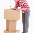 Gorgeous woman writing on cardboard boxes with a marker while st — Stock Photo #11179217