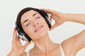 Close up of a delighted brunette listening to music — Stock Photo