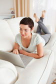 Portrait of a dark-haired woman using a laptop — Stock Photo