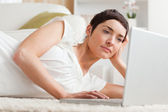 Close up of a serious woman relaxing with a laptop — Stock Photo