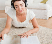 Kvinna läser en tidning medan du njuter av lite musik — Stockfoto