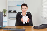 Office worker holding a piggybank — Stock Photo